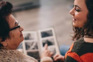 Young woman looking at a photo-album with her grandmother